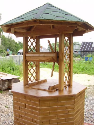 Деревянная крышки в конструкции домика для колодца