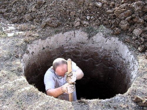 Работа лопатой при рытье колодца