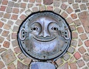 Металлический декоративный люк на канализационном колодце