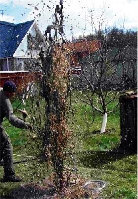 На фото видно, какой фонтан грязи вырывается из скважины во время продувки