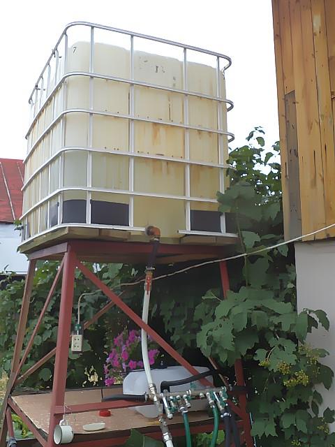 На фото емкость для полива установлена на высокой опоре для подачи воды самотеком