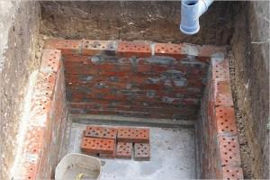 Кирпичная кладка представляется преимущественной, поскольку установка бетонных колец требует подъемные механизмы.