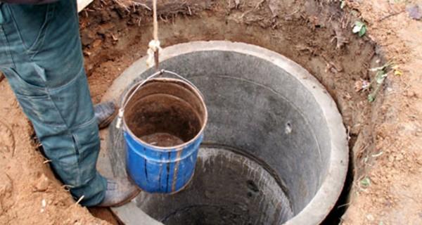 Грунт вынимается из шахты помощником с помощью привязанного к прочной веревке ведра