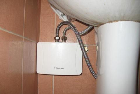 Компактный проточный водонагреватель установлен под умывальником