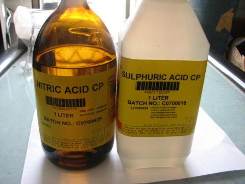 На фото — азотная кислота в стеклянной бутылке и серная кислота в полиэтиленовой таре